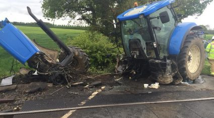 Tractor cut in two after it was hit by a train but the driver survives