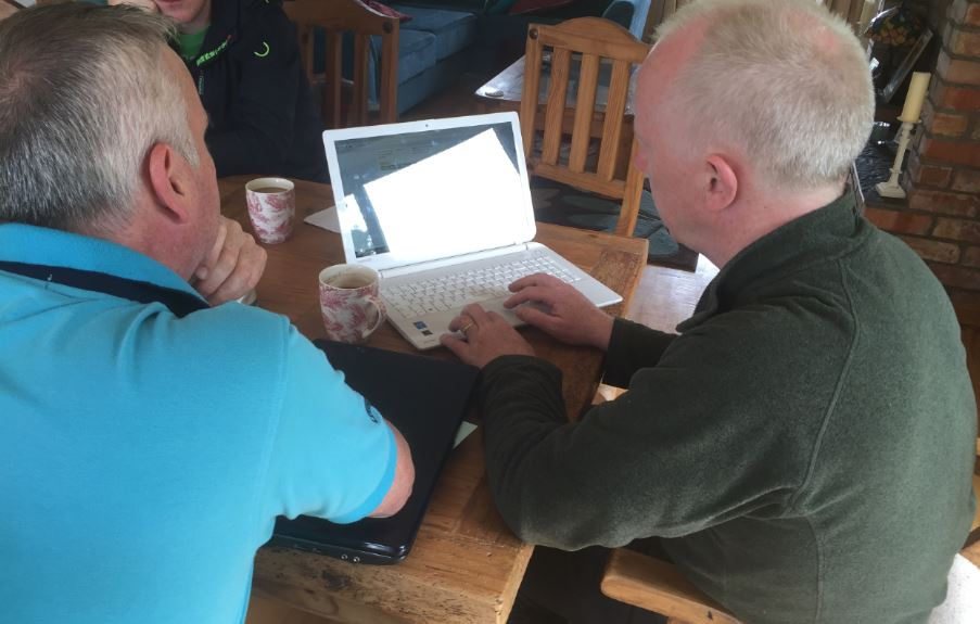 Barry Lynch (left) shows Michael Harlin (right) how to use the Agrinet system