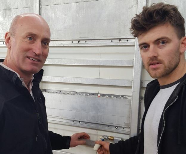 Angus Woods and James Scallan examining a modified teat water feeder, which is necessary on trucks transporting calves to the Netherlands