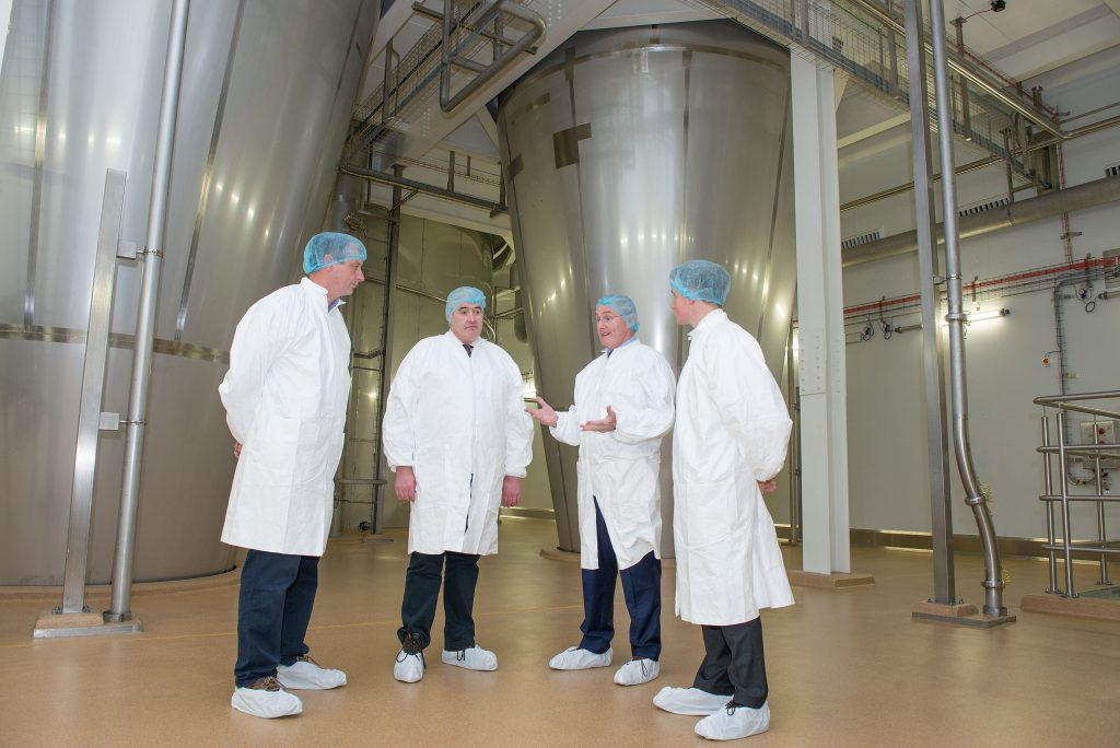 Gabriel D'Arcy, LacPatrick's Chief Executive explains how the two cyclones, pictured behind the group, allow the plant to make infant milk formula.