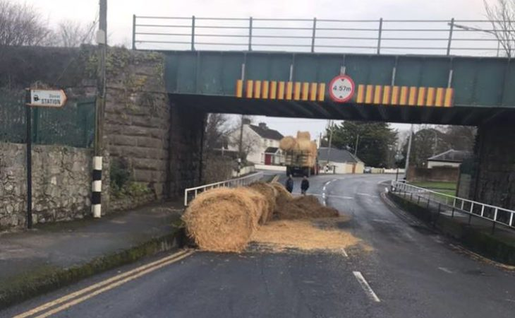 The final 'straw': Tractor carrying bales strikes bridge