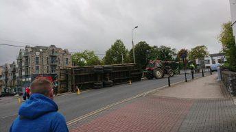 Trailer carrying bales overturns on bridge