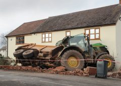 Tractor towing a trailer crashes through the front of a house